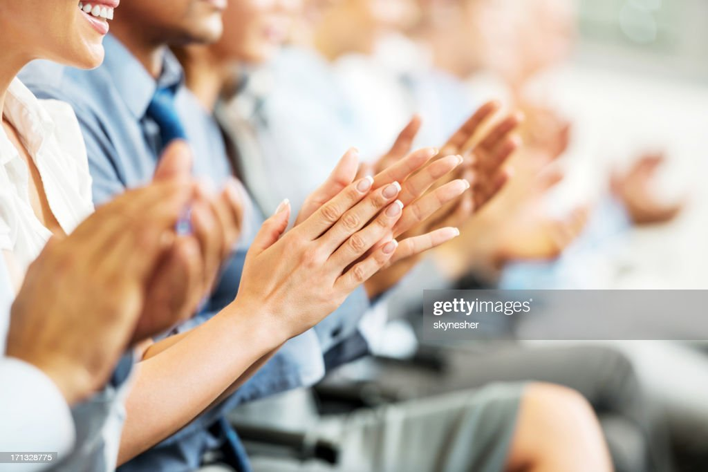 Group of businesspeople sitting in a line and applauding. : Stock Photo