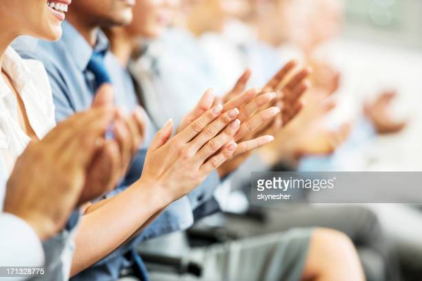 group of businesspeople sitting in a line and applauding. - press conference stock pictures, royalty-free photos & images