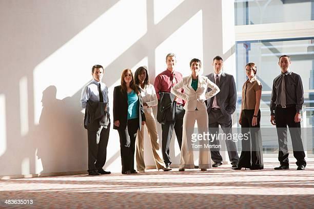 Grupo de empresarios de pie en amplia ventana