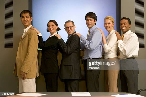 Group of businesspeople standing in row, smiling, portrait