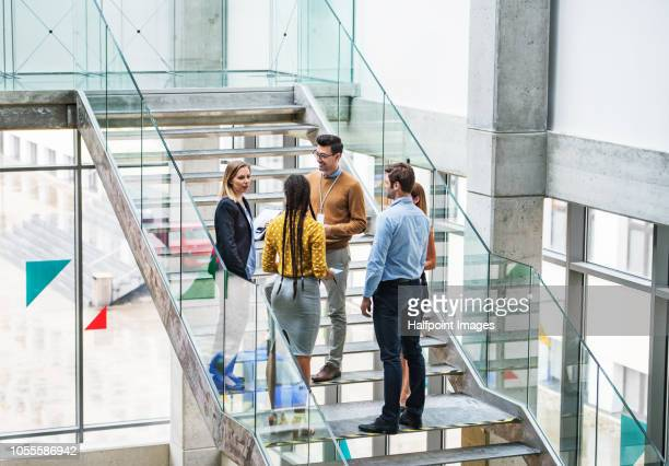 A group of businesspeople standing on the stairs in the modern building, talking.