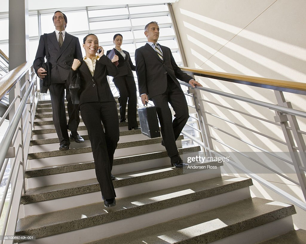 Group of businesspeople walking down stairs, woman using mobile phone : Stockfoto