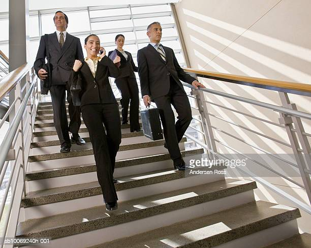 Group of businesspeople walking down stairs, woman using mobile phone