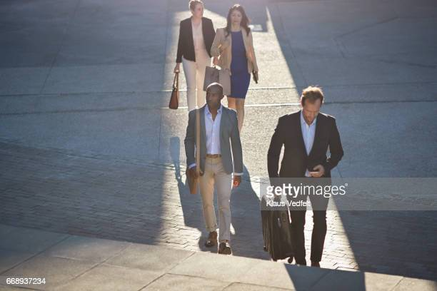 Group of businesspeople walking on staircase with phones and bags