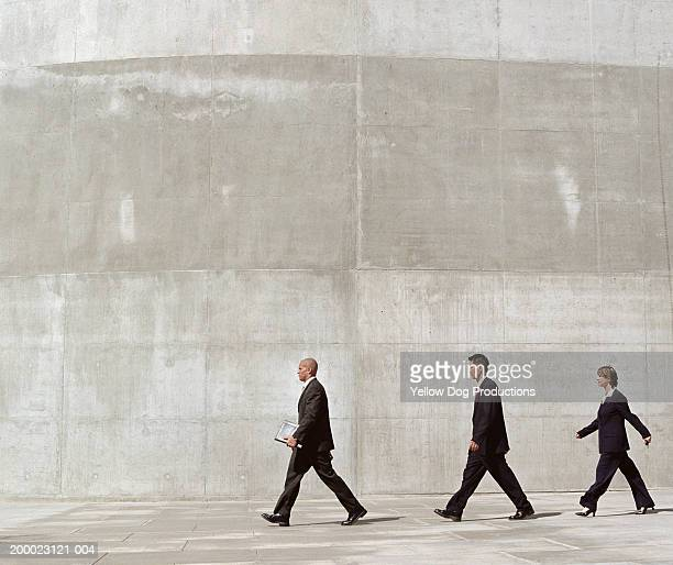 group of businesspeople walking through plaza - gray suit stock pictures, royalty-free photos & images