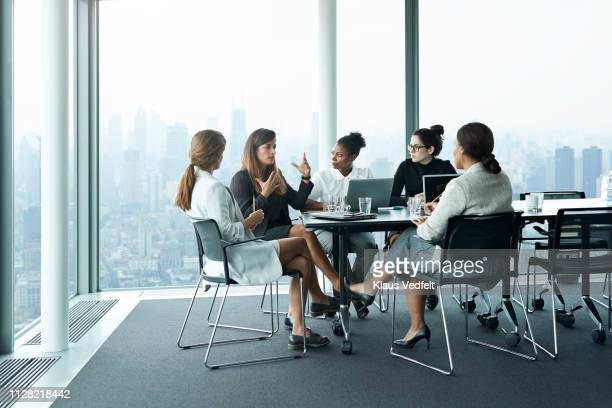 group of businesswomen having meeting in boardroom with stunning skyline view - sólo mujeres fotografías e imágenes de stock