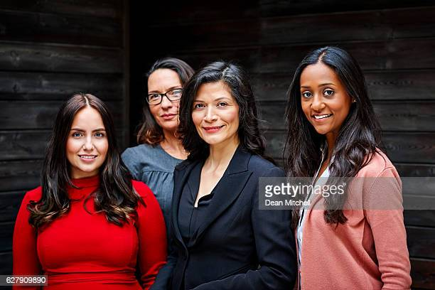 group of businesswomen standing together in office - diverse women fotografías e imágenes de stock
