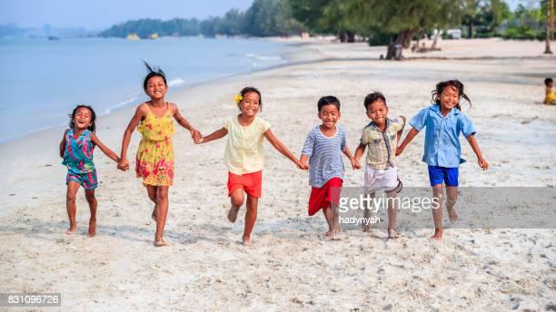 Groupe d'enfants cambodgiens en cours d'exécution sur la plage, Cambodge