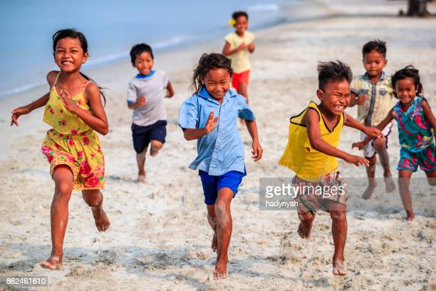 group of cambodian children running on the beach, cambodia - cambodia stock pictures, royalty-free photos & images