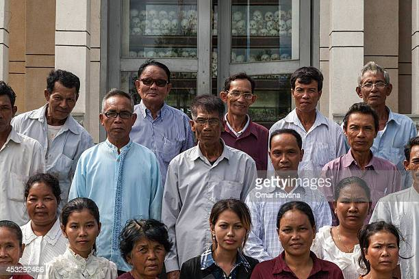 A group of Cambodian survivors pose in front of the main stupa in Choeung Ek Killing Fields which is filled with thousands of skulls of those killed...