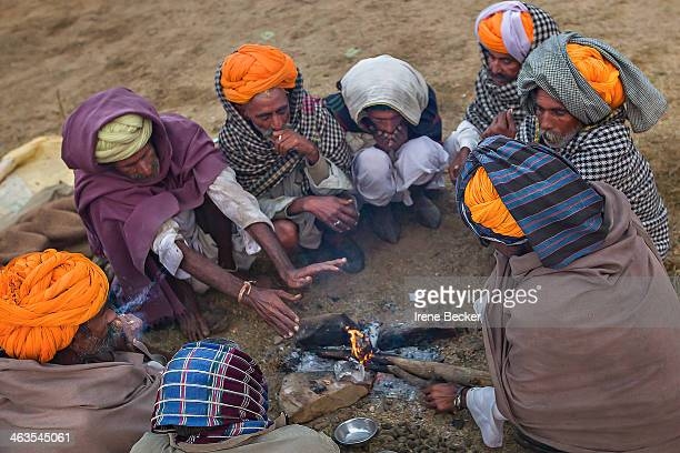 Group of camel traders light fire early in the morning to warm themselves. Pushkar, Rajasthan, India.