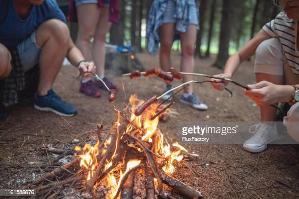 キャンプファイヤーの上にソーセージを調理するキャンパーのグループ - 暖炉の火 ストックフォトと画像