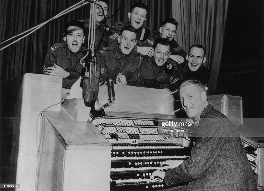 A group of Canadian soldiers take part in a 'Sandy's Half Hour' a BBC radio music programme featuring British theatre and radio organist Sandy MacPherson (right), London, 12th August 1940.