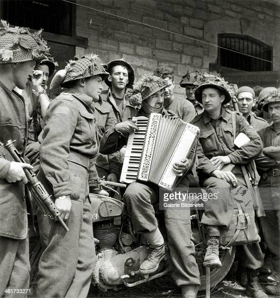Group of Canadians from the Highland Light Infantry of Canada of the 9th Infantry Brigade of the 3rd Canadian Infantry Division is listening to...