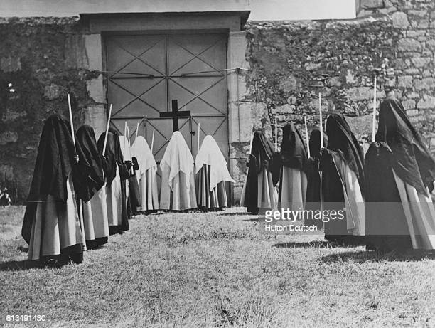 Group of Carmelite nuns, including sisters and novices, walk in a procession towards a doorway.