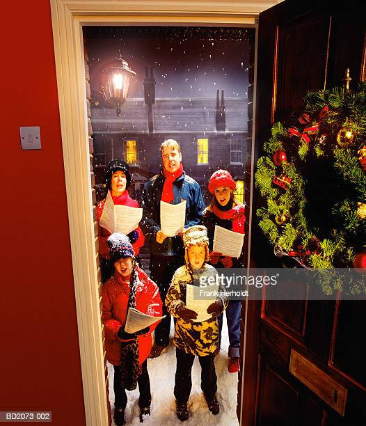 Group of carol singers outside house, view from indoors