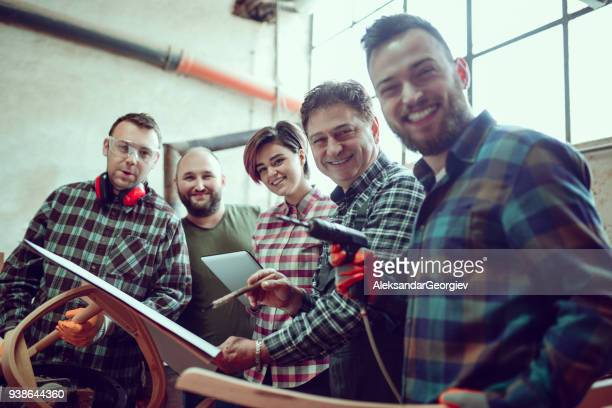 Group of Carpenters Learning How to Use a CNC Machine and Posing in Factory