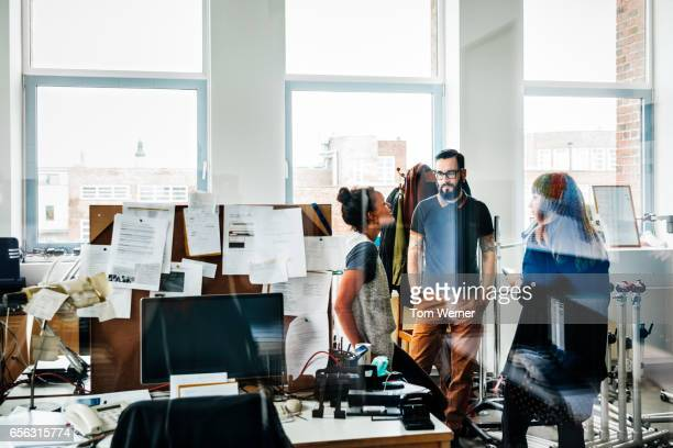 group of casual business people having an informal meeting - photographed through window stock pictures, royalty-free photos & images