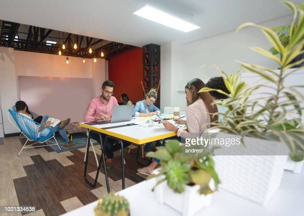 Group of casual business people working at a co-working space