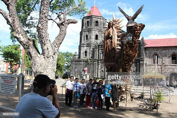 Group of catholic devotees taking a picture in front of statue of Saint Maria of Guadalupe with San Ildefonso De Toledo entitled Pamana ng Tanay...