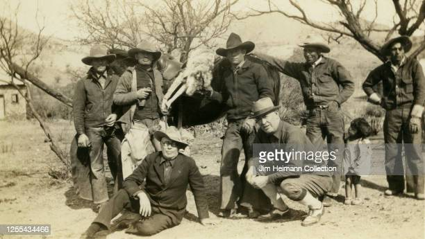 A group of cattlemen cowboys and vaqueros pose with a young girl in front of a horse with a dead wolf slung over its back in Texas circa 1938