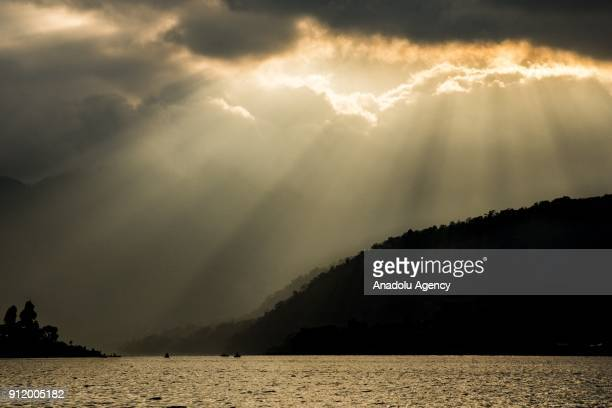 Group of cayucos sit in the mouth of a small bay as the sun set streams through the clouds over Lake Atitlan, Guatemala on January 22, 2018.