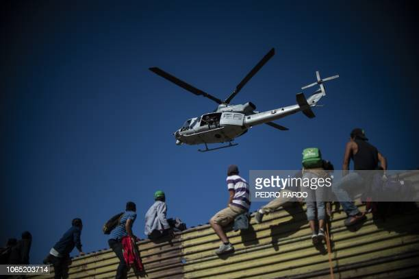TOPSHOT A group of Central American migrants climb the border fence between Mexico and the United States near El Chaparral border crossing in Tijuana...