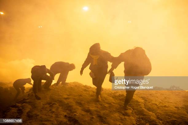 A group of Central American migrants flee the tear gas that the border police threw into Mexican territory to prevent them from entering illegally on...