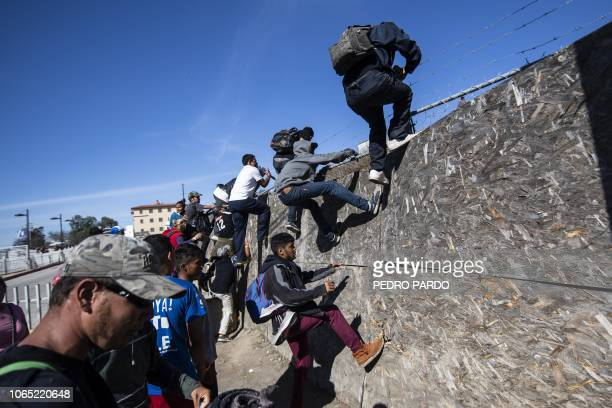 TOPSHOT A group of Central American migrants mostly from Honduras get over a fence as they try to reach the USMexico border near the El Chaparral...