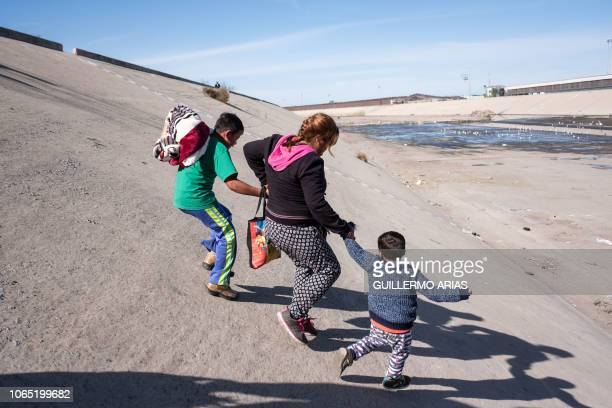 A group of Central American migrants mostly from Honduras run along the dry riverbed of the Tijuana River in an attempt to get to El Chaparral port...