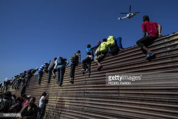 TOPSHOT A group of Central American migrants mostly Hondurans climb a metal barrier on the MexicoUS border near El Chaparral border crossing in...