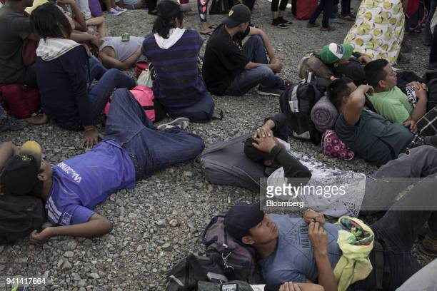 A group of Central American refugees and asylum seekers led by the nonprofit humanitarian organization Pueblos Sin Fronteras rest along a road in the...