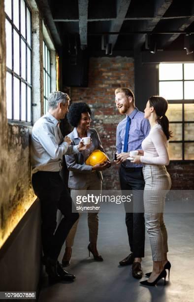 gruppo di allegri colleghi di lavoro che comunicano una pausa caffè in ufficio. - fare una pausa foto e immagini stock