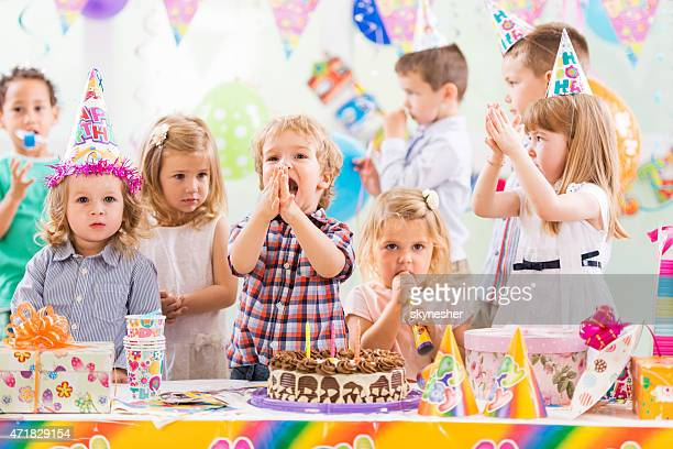 Group of cheerful children celebrating birthday and singing.