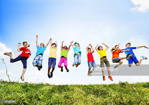 Group of cheerful children jumping against the sky.