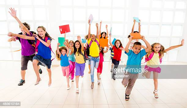 Group of cheerful children running with backpacks and books.