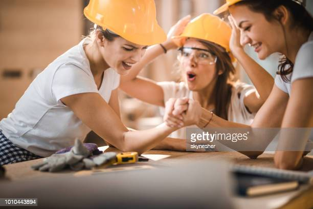 Group of cheerful construction workers having fun while arm wrestling during home renovation process.