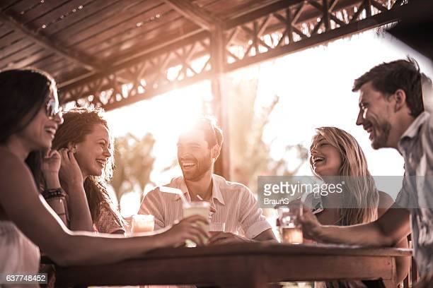 Group of cheerful friends having fun while taking in bar.