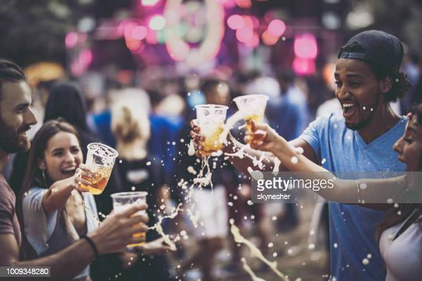 group of cheerful friends having fun with beer on a music concert. - beer alcohol stock pictures, royalty-free photos & images