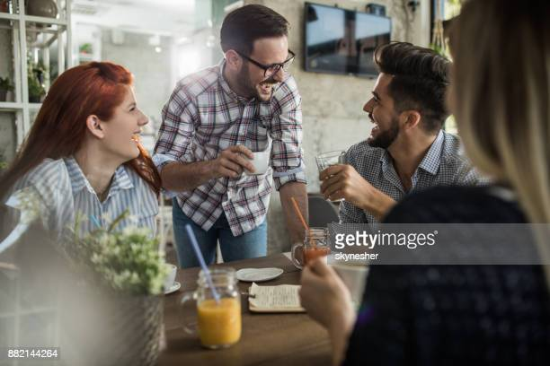 Group of cheerful friends talking about something funny in a cafe.