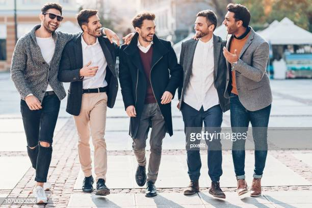 group of cheerful male friends on the street - smart casual stock pictures, royalty-free photos & images
