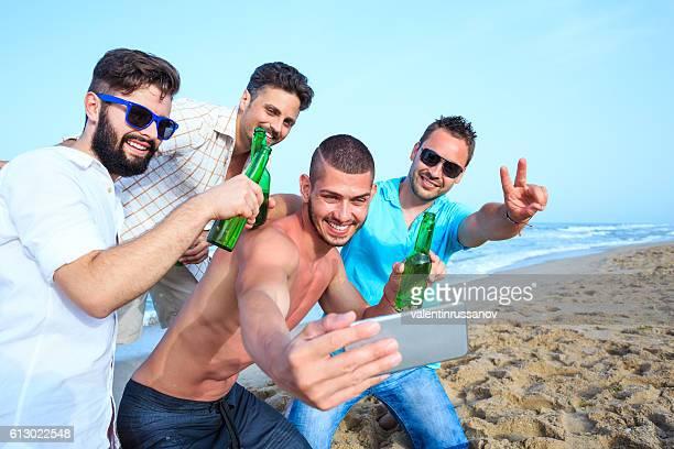 Group of cheerful men making selfie on beach
