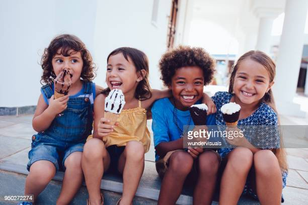 group of cheerful multi-ethnic children eating ice-cream in summer - family vacation stock pictures, royalty-free photos & images