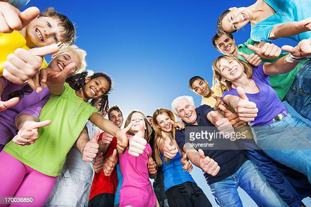 Group of cheerful people against the blue sky.