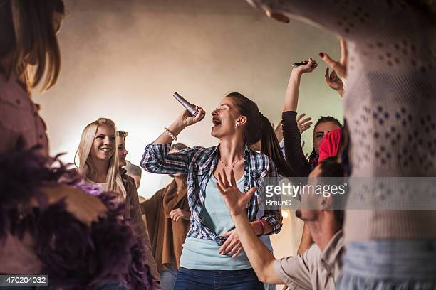 group of cheerful people having karaoke party at disco. - karaoke stock pictures, royalty-free photos & images