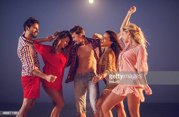 Group of cheerful people on a beach party at night.