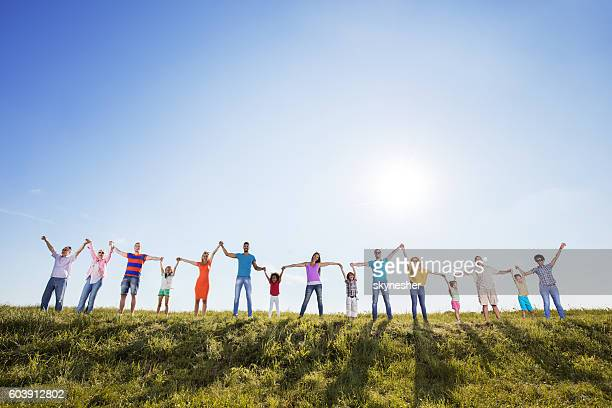 group of cheerful people standing in nature and holding hands. - さまざまな年齢層 ストックフォトと画像