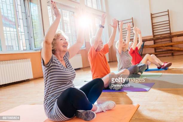 group of cheerful seniors doing yoga together