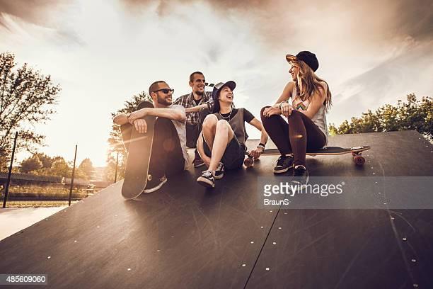 グループの楽しい会話にたむろうスケートのランプを降ります。