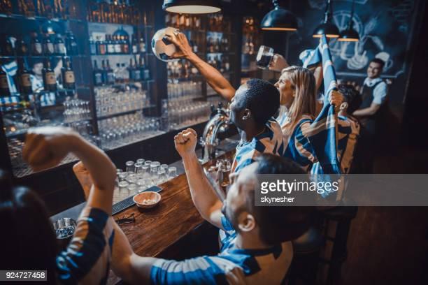 gruppe von fröhlichen fußball-fans feiern sieg ihrer mannschaft während gerade ein spiel in einer bar. - weltmeisterschaft stock-fotos und bilder